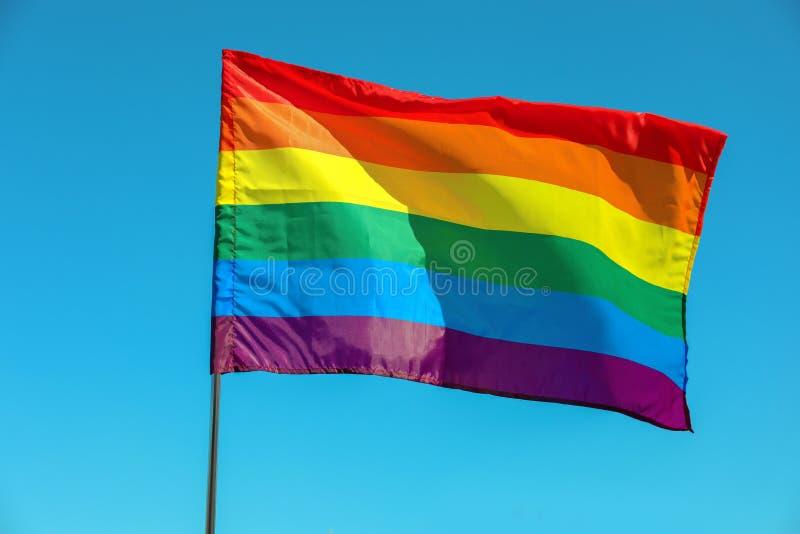 Waving rainbow LGBT flag against blue sky royalty free stock photography