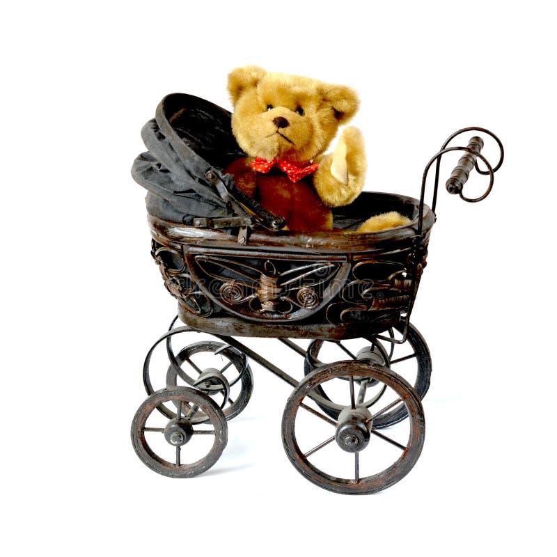 Waving teddy bear in vintage pram. Soft fluffy teddy bear waving while sitting in a vintage style pram/stroller. Copy space stock images