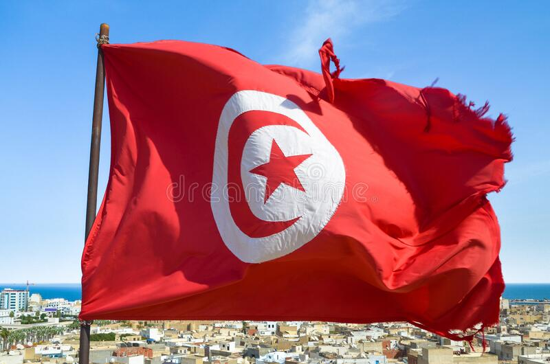 Waving tunisian flag on the background of the medieval medina in Sousse, tunisia. royalty free stock photos