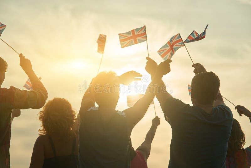 Waving UK flags. British people against morning sunshine background royalty free stock photos