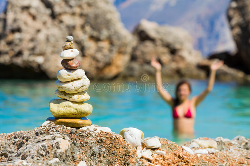 Waving from water. Rocks put together with attention, happy woman in the background symbolizing vacation and balance stock image