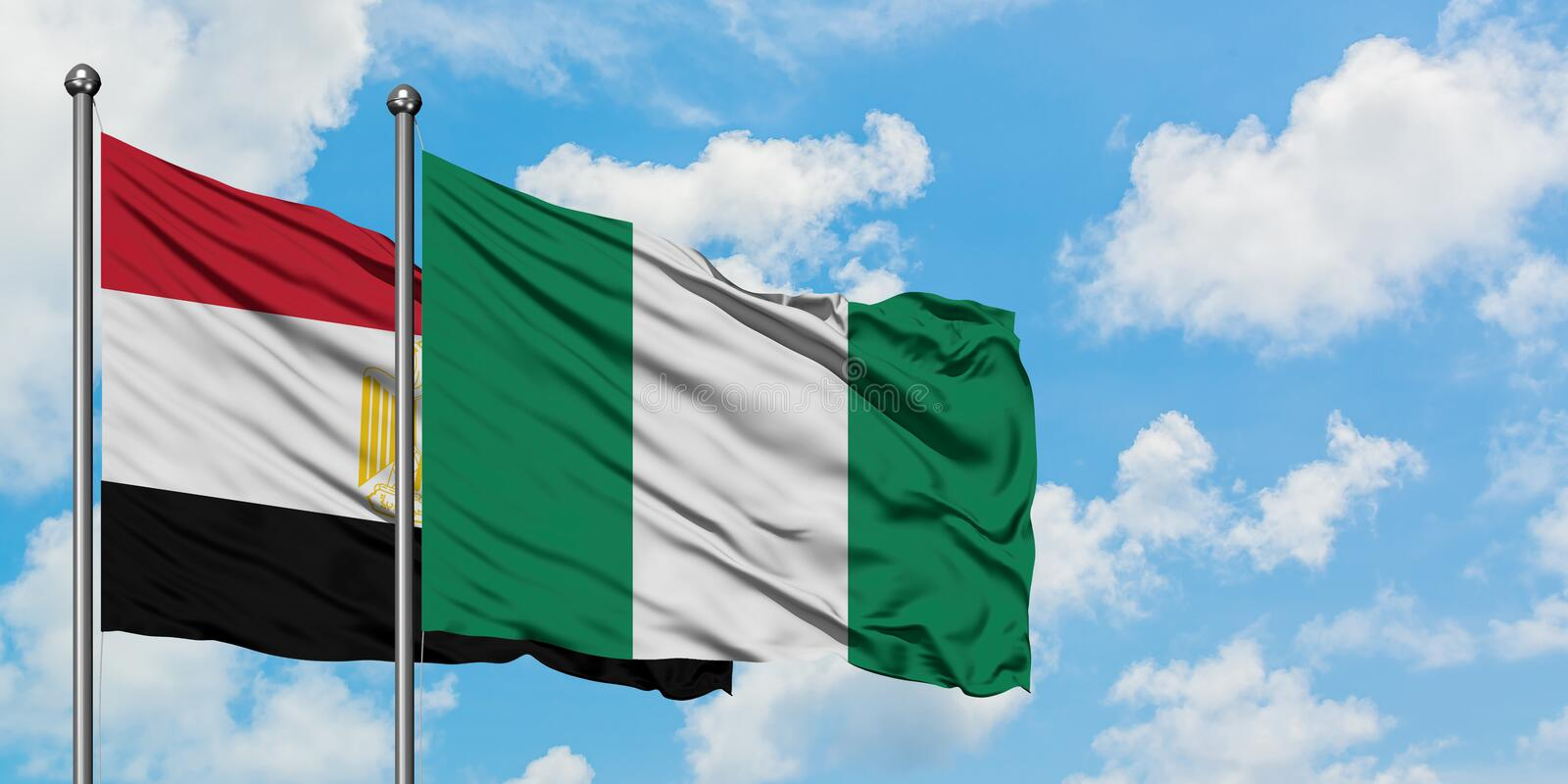 Egypt and Nigeria flag waving in the wind against white cloudy blue sky together. Diplomacy concept, international relations. Waving in the wind against white royalty free stock photo