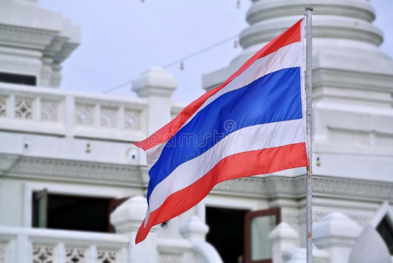 Wavy Flag of Thailand on the Post at the Buddhist Temple stock photo