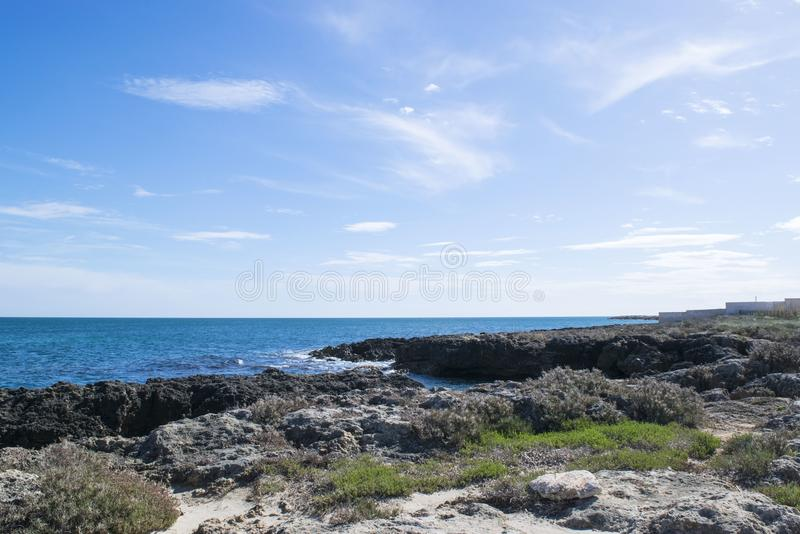 Wavy Sea Beside Rock Formations Near Sea Shore With Grasses Under Blue Cloudy Sky at Daytime royalty free stock photography
