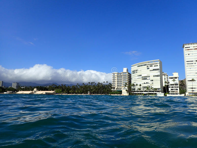 Wavy water on ocean off Kaimana Beach with hotels and condos stock photography