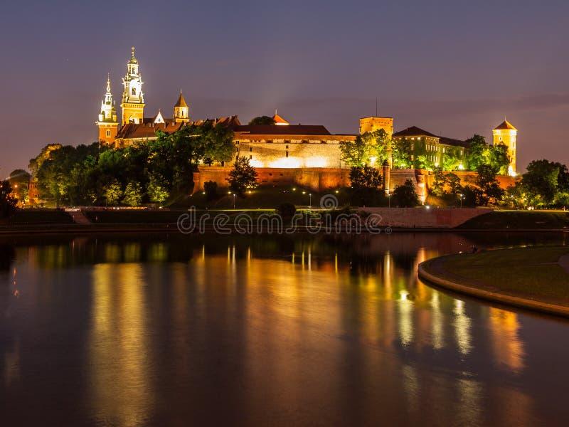 Wawelkasteel en Vistula-rivier bij nacht stock foto's