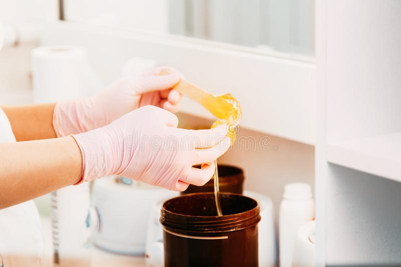 Wax bar with sugar paste depilation and beauty concept - sugar paste or wax honey for hair removing. With purple gloves hands of cosmetologist in spa salon. Top stock image