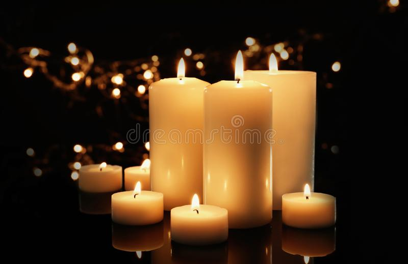 Wax candles burning against blurred lights stock photography