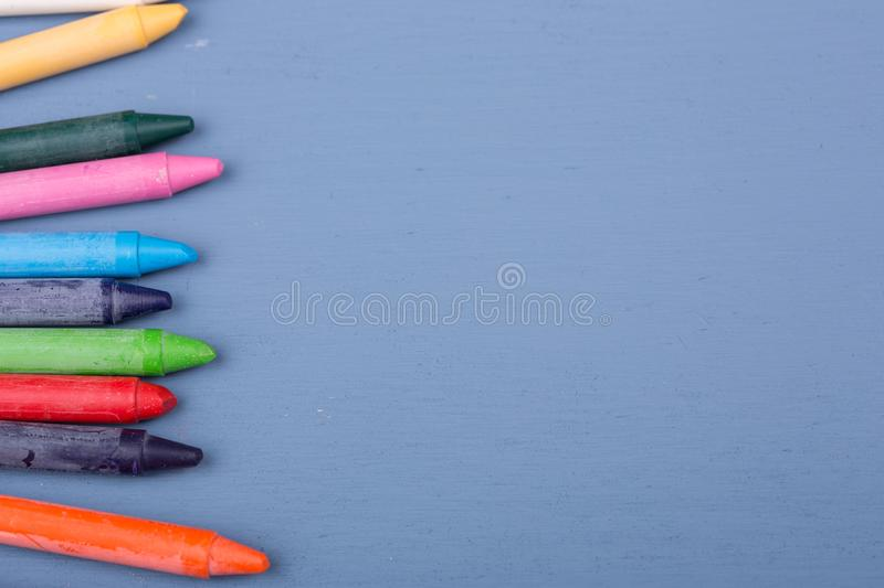 Wax crayons. On a blue wooden background stock photography