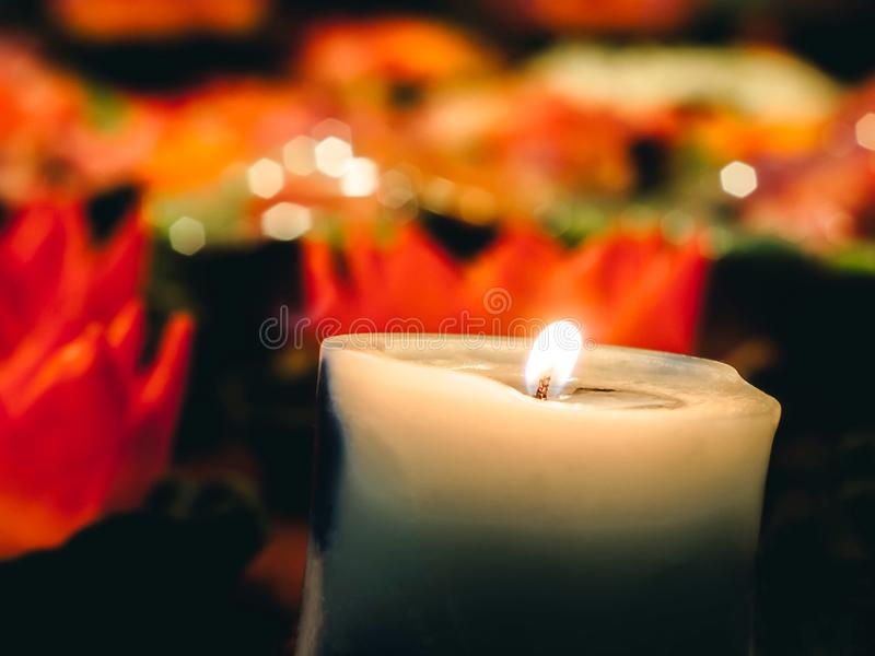 A wax or tallow with a central wick that is lit to produce light as it burns. Many burning candles with shallow depth of field, stock photo