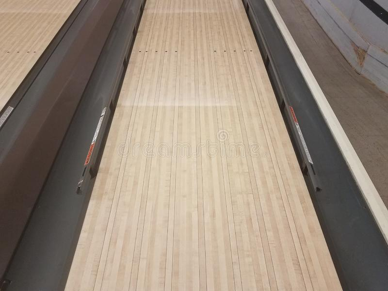 Waxed wooden bowling alley lanes with bumpers stock images