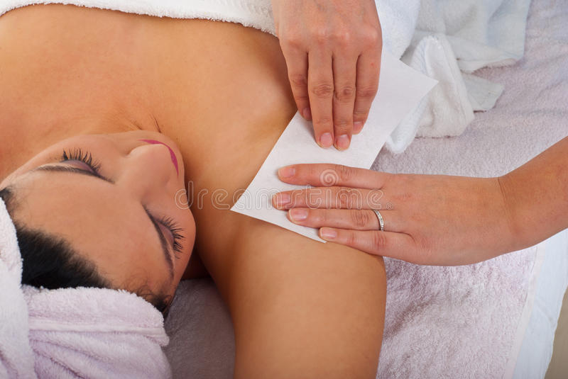 Waxing armpit. Beautician waxing armpit to a woman in a salon