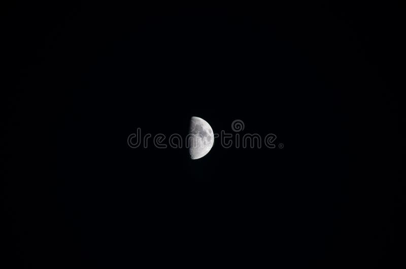 Waxing Moon First Quarter. The waxing first quarter moon brightens a dark autumn sky royalty free stock photography