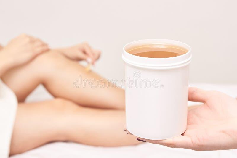 Waxing woman leg. Sugar hair removal. laser service epilation. Salon wax beautician procedure stock images