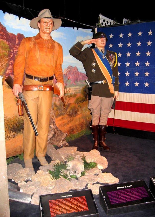Waxworktablå av John Wayne som Hondo och George C Scott som Patton royaltyfria bilder