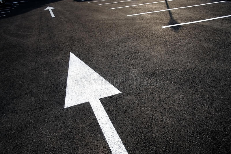 This way. Strong directional white arrow and markings painted on textured black asphalt. Leadership and strategy concept. Strategic planning, solution / stock image