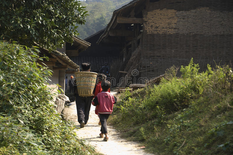 On the way home. Lived in a village in the mountain villagers of the miao nationality, they carry a basket items, zhuang walk home with the children of the path stock photos