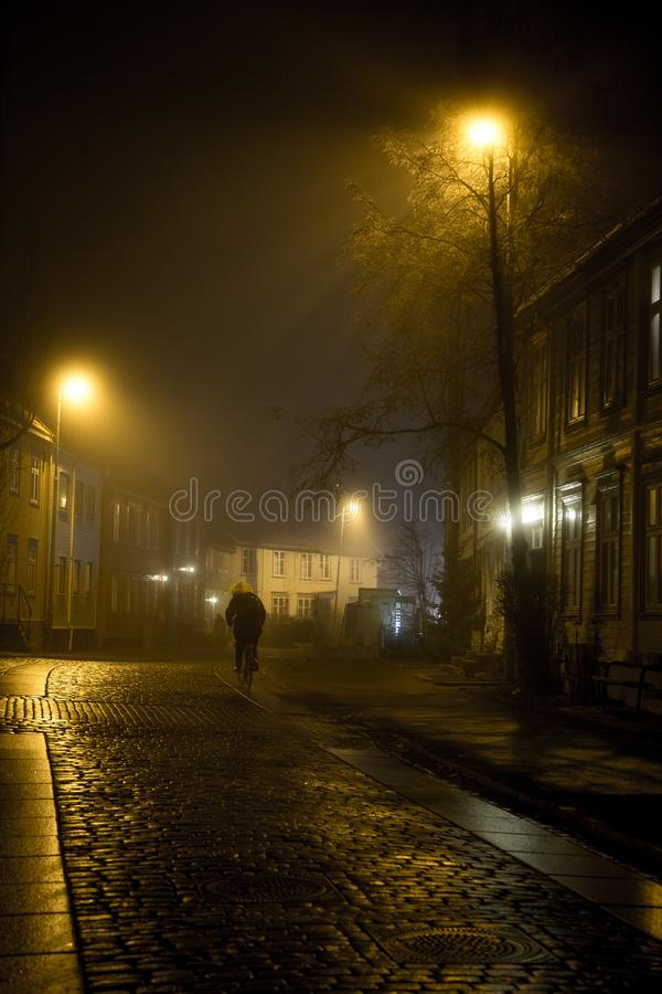 On the way home - single man on the Baklandet foggy streets, night walk in Trondheim`s old town stock image