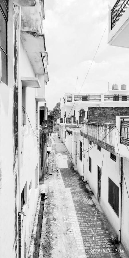 Black and white portrait of a vacant or no man street during miday of summer . Electricity wires from house . Life. The houses are located both sides of a royalty free stock image