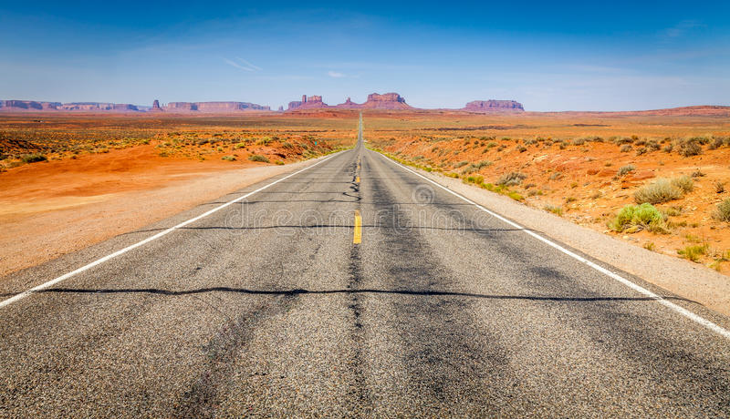 The way. Straight road leading to the fabulous Monument Valley National Park in Utah stock photos