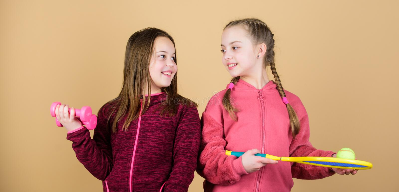 On the way to perfect shape. Happy children with sport equipment. gym workout of teen girls. Tennis racket and ball for stock photos
