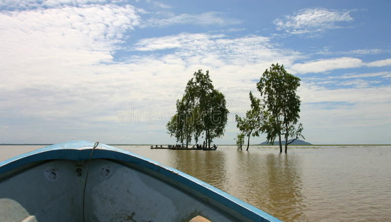 Way to Phnom Da near Takeo. Cambodia. On the way to temple of Phnom Da. Wet season. Fishermen rest in shade of trees in flooded fields. Near town of Takeo stock photo