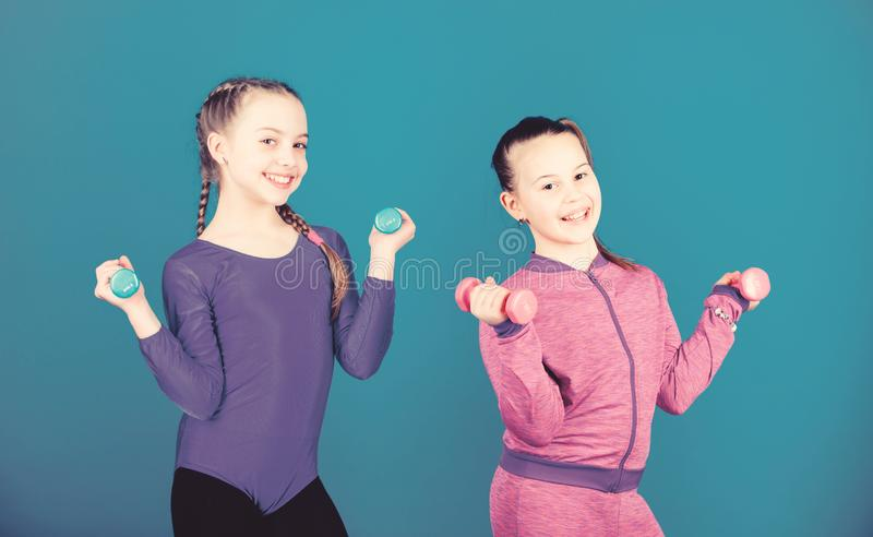 On way to stronger body. Girls exercising with dumbbells. Beginner dumbbells exercises. Children hold dumbbells blue. Background. Sport for teens. Easy stock photos