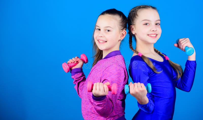 On way to stronger body. Girls exercising with dumbbells. Beginner dumbbells exercises. Sporty upbringing. Children hold. Dumbbells blue background. Sport for stock images