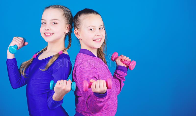 On way to stronger body. Girls exercising with dumbbells. Beginner dumbbells exercises. Sporty upbringing. Children hold. Dumbbells blue background. Sport for stock photos