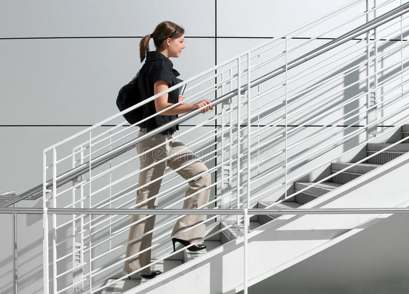 A way to success. A girl college student walking up the staircase royalty free stock photos