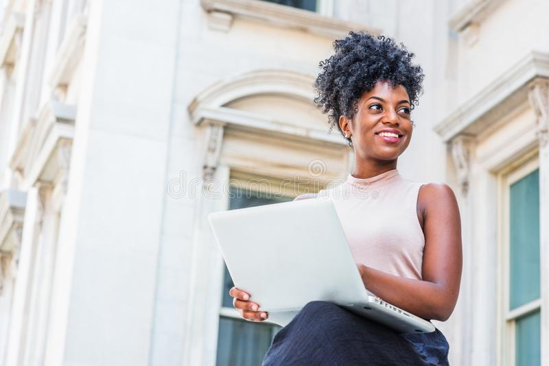 Way to Success. Young African American woman with afro hairstyle wearing sleeveless light color top, sitting by vintage office stock photo