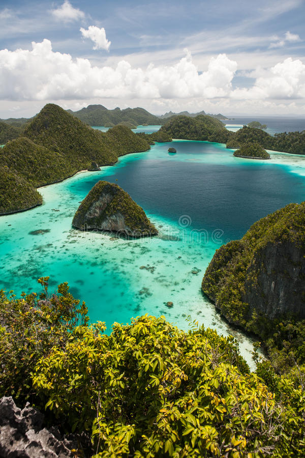 Wayag Lagoon in Raja Ampat. Limestone islands surround a beautiful lagoon in Wayag, Raja Ampat, Indonesia. This remote, tropical region is known for its stock images
