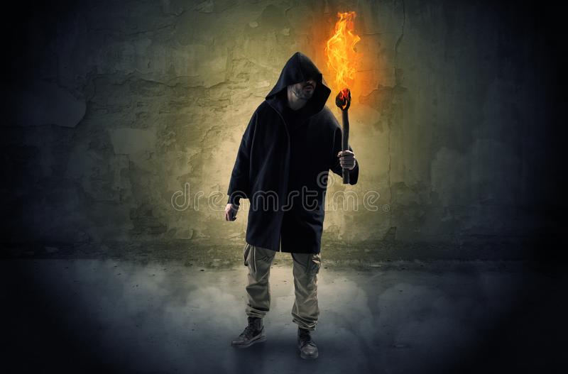 Wayfarer with burning torch in front of crumbly wall concept. Ugly wayfarer with burning torch in his hand in front of a crumbly wall concept stock photo