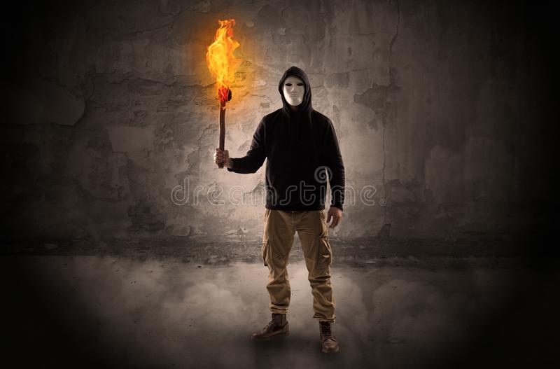 Wayfarer with burning torch in front of crumbly wall concept. Ugly wayfarer with burning torch in his hand in front of a crumbly wall concept stock image