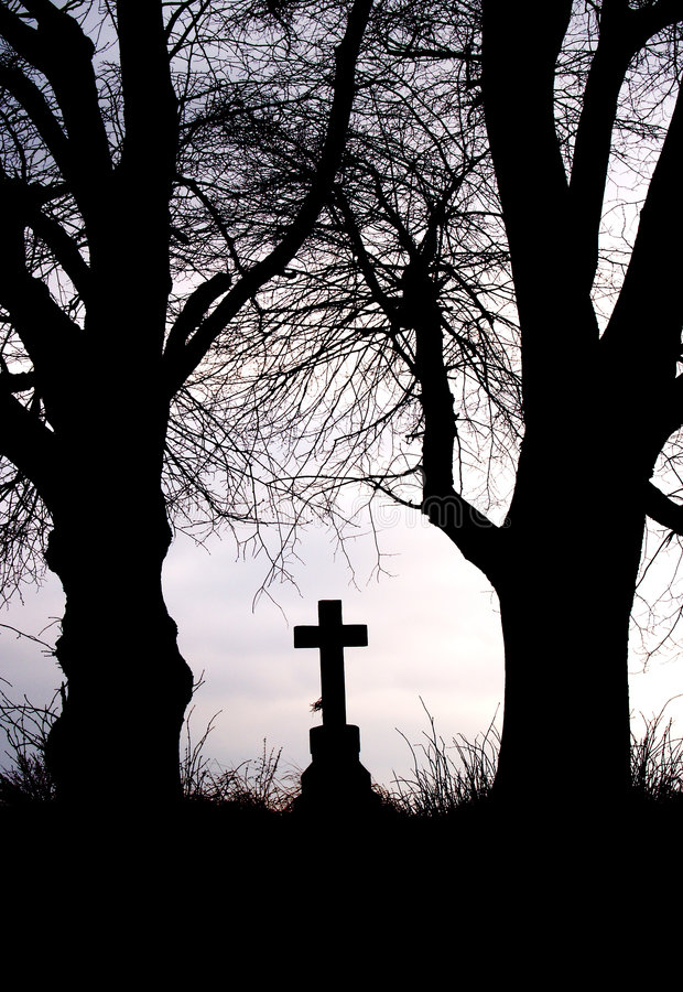Wayside cross. Silhoutte of christian wayside cross between old trees royalty free stock photography