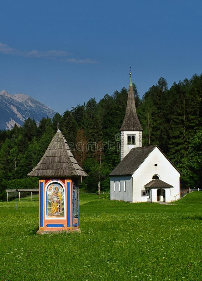 Wayside shrine and chapel in Alpine meadow stock photography