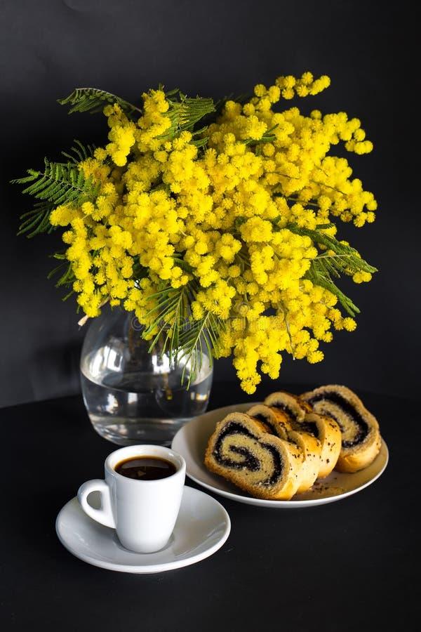 Waza z mimoz, filiżanki kawy i makowego ziarna strudlem na czarnym tle, zdjęcie royalty free