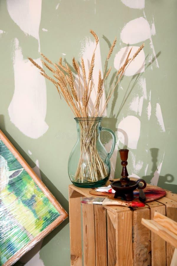 Waza z spikelets z farb dostawami na drewnianej skrzynce w artyście, s warsztacie « obraz royalty free