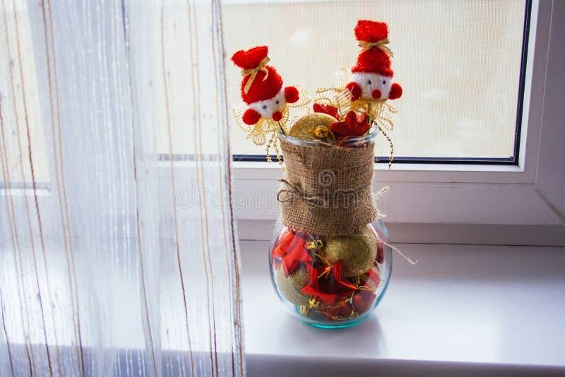 Wazy stojaki przy okno, zawijający w parcianym i wypełniający z czerwonymi i żółtymi choinek zabawkami zdjęcie stock