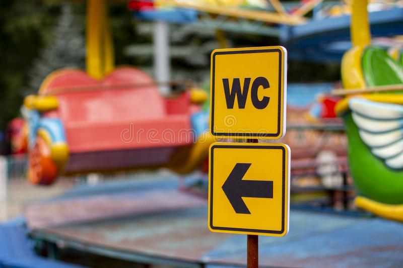 WC sign on a yellow plate with arrow pointer. Sign pointer where the toilet is located royalty free stock image