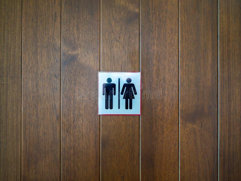 WC/toaletttecken-, man- och damsymbol på träbakgrund royaltyfria bilder