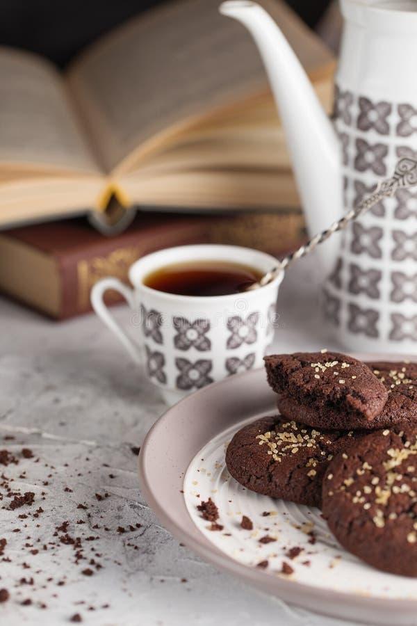 Wciąż życie skład czekoladowi ciastka na talerzu, filiżance, kawowym garnku i książkach, Karmowa fotografia obrazy royalty free