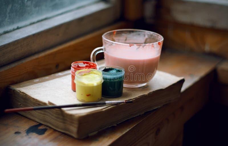 Wciąż maluje życie guasz, muśnięcia, farby rozcieńczenia filiżanka i książka, fotografia stock
