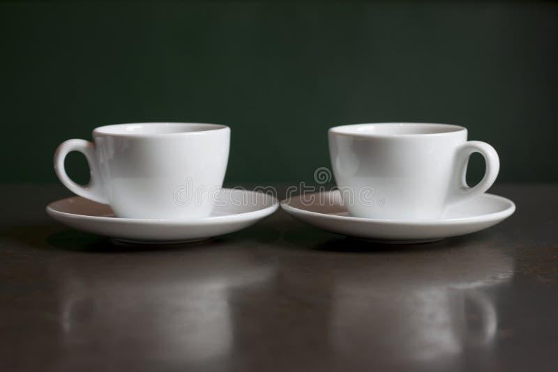 Wciąż życie, biały czajnik i filiżanki na stole, zdjęcie stock