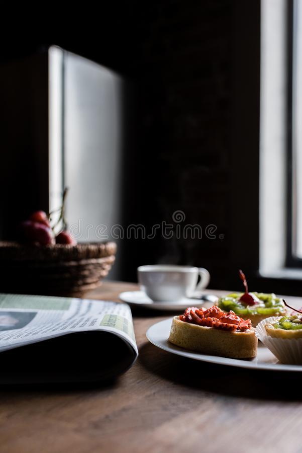 Wciąż życie gazeta, śniadanie z tortami i gorąca kawa na kuchennym stole w przodzie, obraz stock