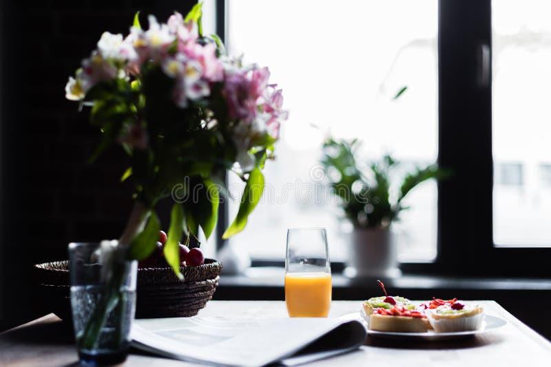 Wciąż życie gazeta, śniadanie z tortami i szkło sok na kuchennym stole w przodzie, fotografia stock