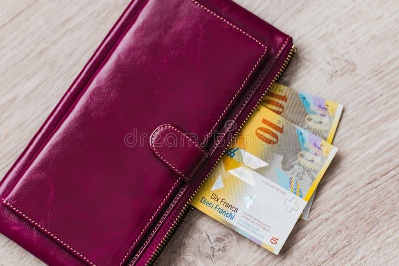 Wciąż życie gotówka Bordoski rzemienny portfel i Szwajcarscy franki na drewnianym tle fotografia stock