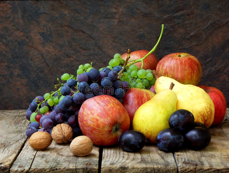 Wciąż życie jesieni owoc: winogrona, jabłka, bonkrety, śliwki, dokrętki fotografia stock