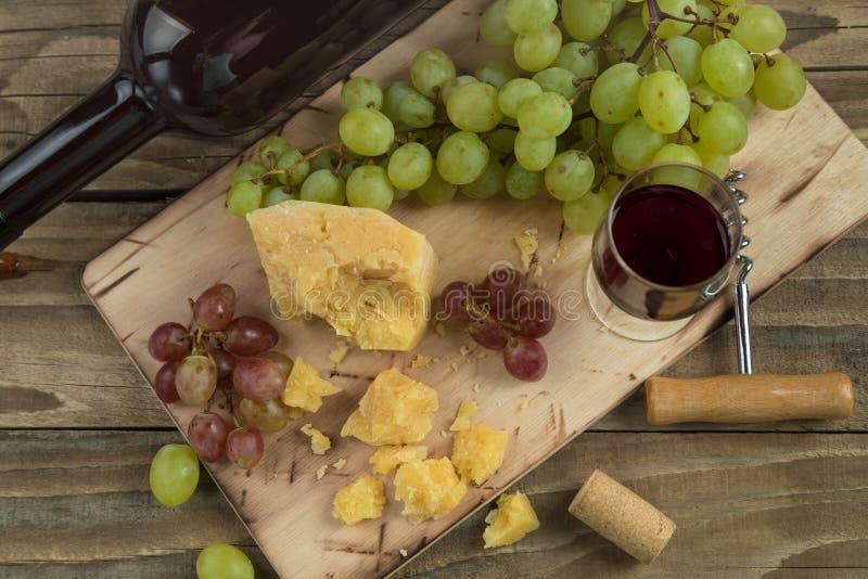 Wciąż życie od jedzenia i wina Kawałek ciężki ser kłama na ciapanie desce Grona czerwień i zieleń dorośleć winogrona, zmrok fotografia royalty free