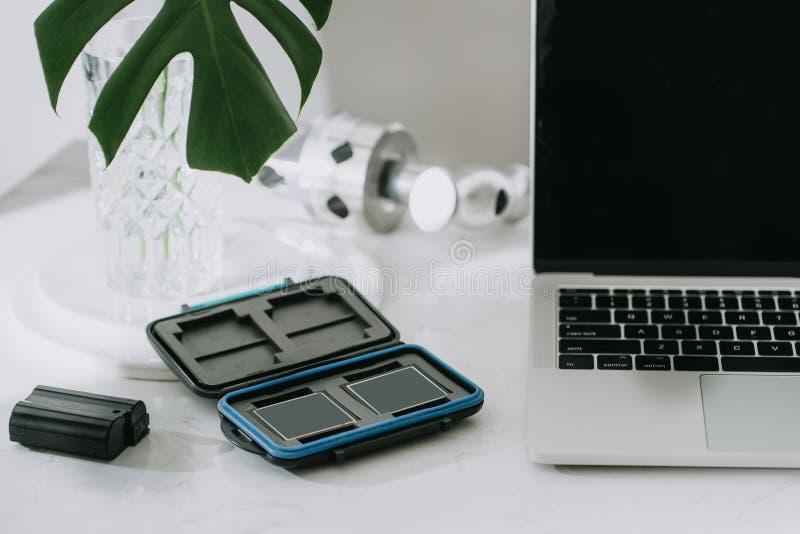 Wciąż życie pracuje od domowego biurka z fachowym fotograficznym wyposażeniem, kamera, obiektyw, komputerowy monitor, elektronika zdjęcia stock
